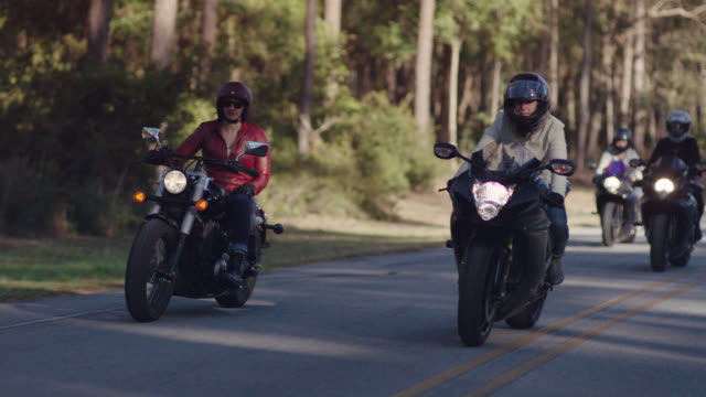 slo mo. four women on motorcycles cruise down wooded highway in group formation. - motorradfahrer stock-videos und b-roll-filmmaterial