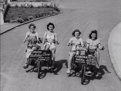 four women ride peddle bikes at the coronation holiday camp on hayling island. - holiday camp stock videos & royalty-free footage
