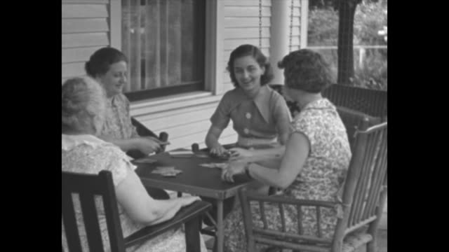 vidéos et rushes de four women sit at table on porch and play cards, one woman deals / woman squatting in garden pruning flowers / note: exact day not known - cartes à jouer