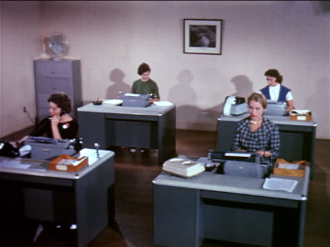 1961 four women sitting at desks typing on typewriters / one using dictaphone / one on telephone - sekretärin stock-videos und b-roll-filmmaterial