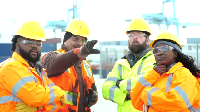 four workers talking, working at shipping port - safety stock videos & royalty-free footage
