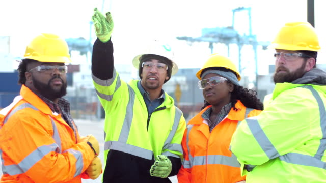 four workers talking, working at shipping port - hard hat stock videos & royalty-free footage