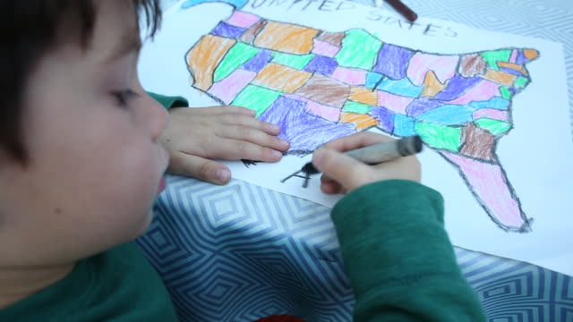 vídeos y material grabado en eventos de stock de a four year old boy drawing and creating a map outside at a picnic table. - identidad