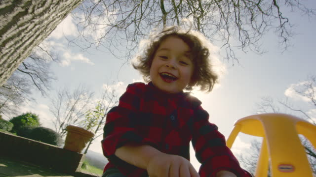 a four year old boy riding a toy car around the garden in a check shirt - boys stock videos & royalty-free footage