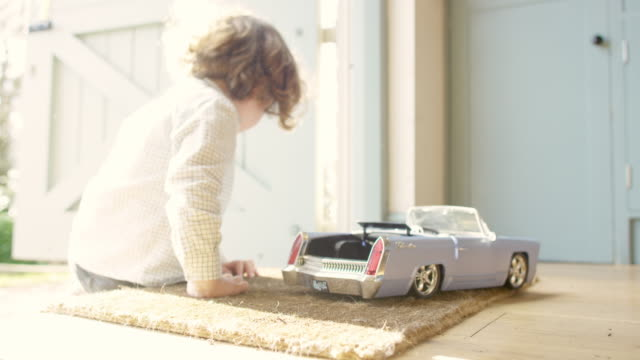 A four year old boy sitting at a back door playing with a toy car
