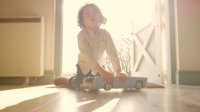 vídeos de stock, filmes e b-roll de a four year old boy sitting at a back door playing with a toy car - brinquedo