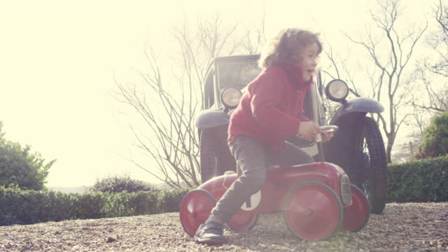 a four year old boy sitting sitting on a toy tractor by a vintage car - vintage car stock videos & royalty-free footage