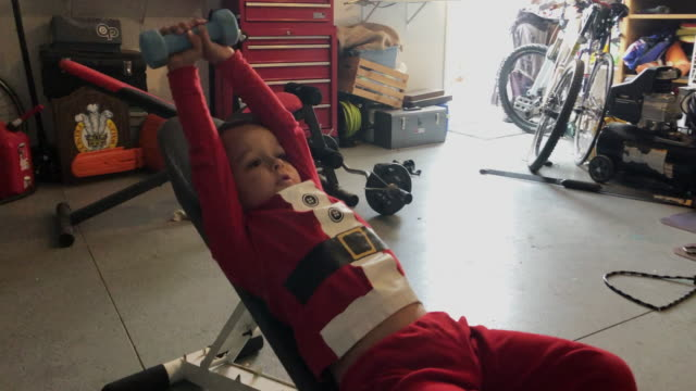 a four year-old caucasian boy in christmas pajamas lifts a dumbbell into the air while lying on an exercise bench in a residential garage - weight training stock videos & royalty-free footage