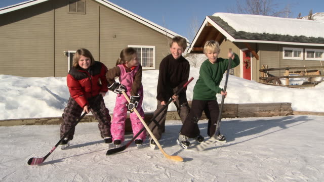 four young kids bang their hockey sticks on backyard ice rink / bellevue, idaho, united states - ホッケー点の映像素材/bロール