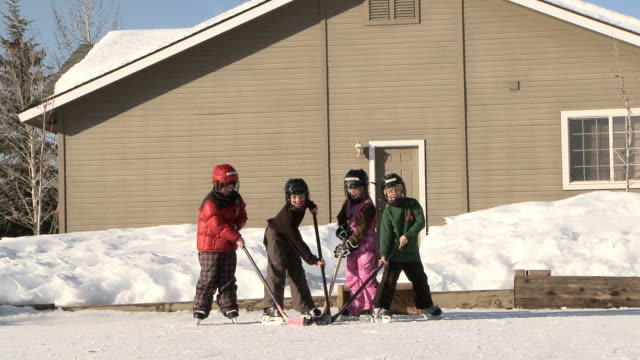 four young kids play hockey on backyard ice rink / bellevue, idaho, united states - winter sport stock videos & royalty-free footage
