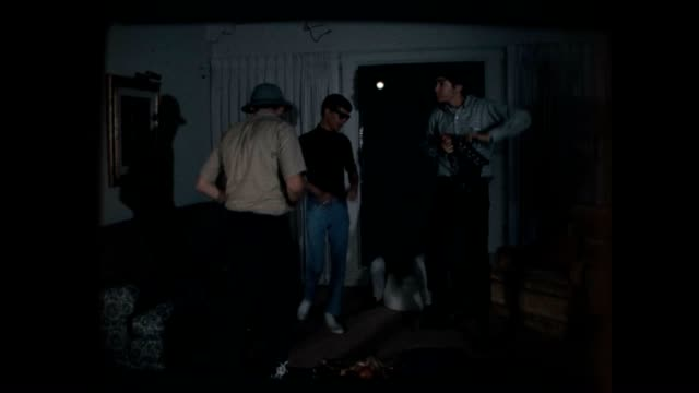 four young men carrying filmmaking props jump and dance comically around a living room / young woman enters the room wanders around and looks confused - film director video stock e b–roll