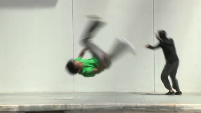 ws slomo four young men do flips and somersaults in street, parkour/singapore - バク転点の映像素材/bロール