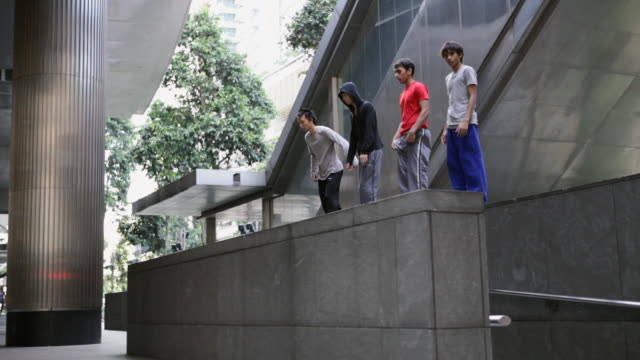 WS Four young men doing somersault off wall Parkour/Singapore