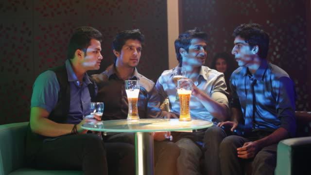vídeos de stock, filmes e b-roll de four young men watching television in a nightclub - perda