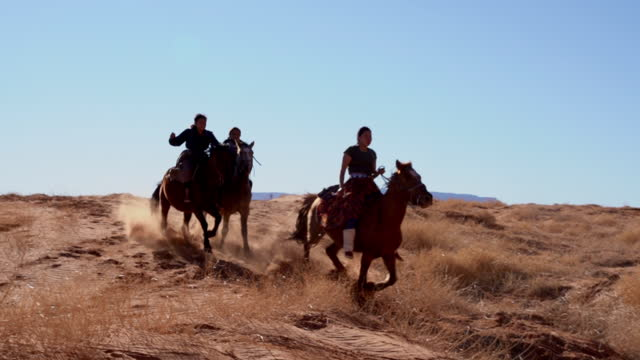 four young native american navajo brothers and sisters riding their horses bareback in the northern arizona monument valley tribal park at dusk together - male with group of females stock videos & royalty-free footage