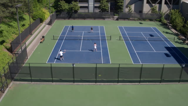four young people playing tennis outdoors - tennis stock videos and b-roll footage