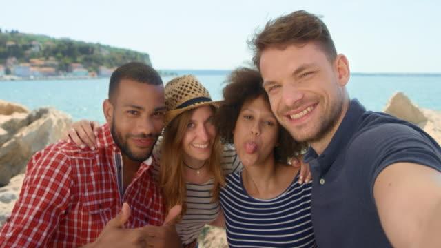 Vier junge Leute unter Selfies am Meer