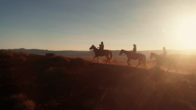 vídeos de stock e filmes b-roll de four young teenage and younger siblings navajo native american people riding their horses bareback in the desert near monument valley tribal park at dusk in the summer - animal family
