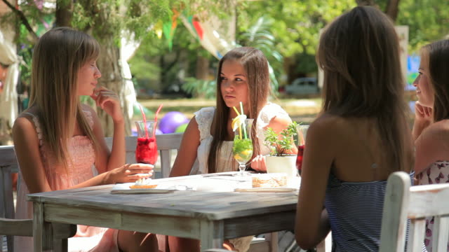 Four young woman in summer outdoors sidewalk cafe