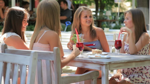 stockvideo's en b-roll-footage met four young woman in summer outdoors sidewalk cafe - koffie drank