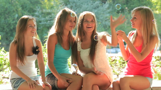 four young woman in summer park fun soap bubbles - four people stock videos & royalty-free footage