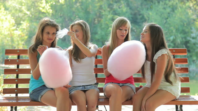 Four young woman in summer park with cotton candy