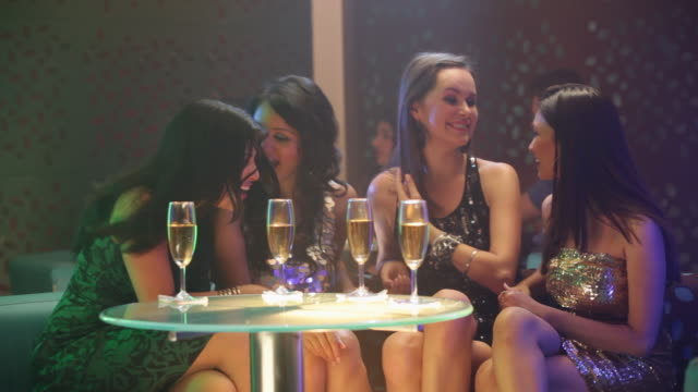 four young women drinking champagne in a nightclub - four people stock videos & royalty-free footage