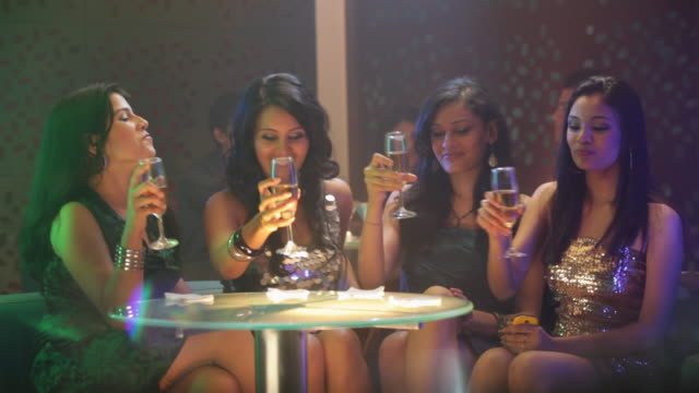 Four young women drinking champagne in a nightclub