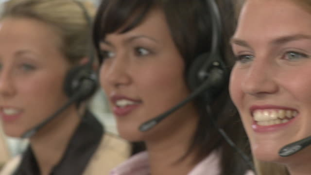 vídeos y material grabado en eventos de stock de ecu, pan, focusing, four young women with headset working in call center - call center latino