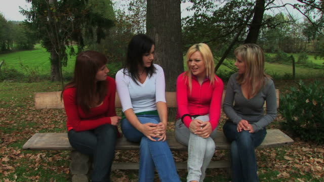 four young womens siting on bench in nature and talk - cross legged stock videos & royalty-free footage
