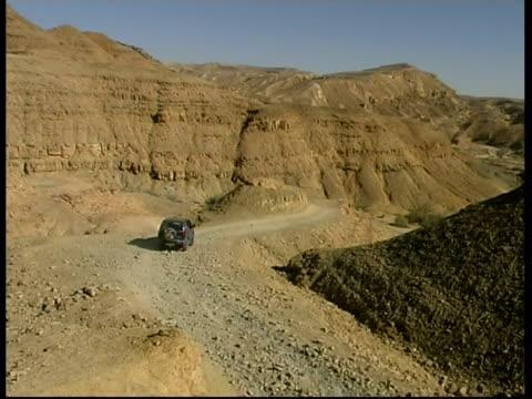 four-by-fours on dust road, negev desert, israel - felswand stock-videos und b-roll-filmmaterial