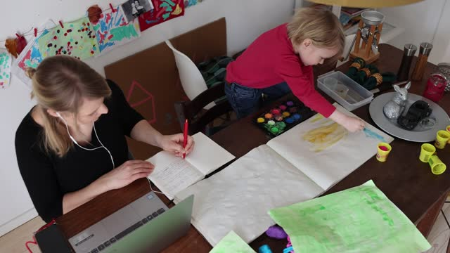 four-year-old boy paints while his mother works and attends a digital conference at home in zehlendorf district during the second wave of the... - working from home stock videos & royalty-free footage