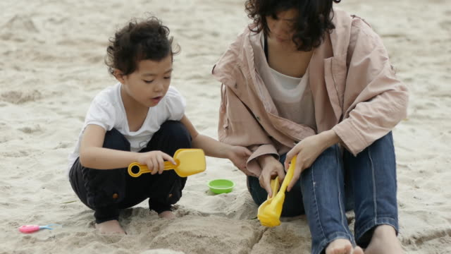 four-years-old asian girl playing with mum on sand, making cake. - assertiveness stock videos & royalty-free footage