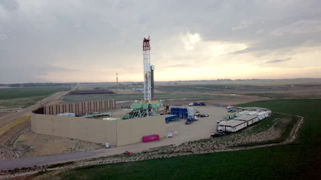 vídeos de stock, filmes e b-roll de fracking perfuração na frente de um céu dramático ao entardecer - poço de petróleo