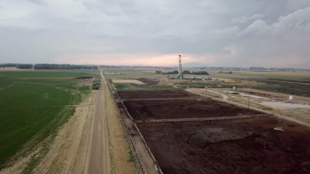 vídeos de stock, filmes e b-roll de fracking perfuração na frente de um céu dramático ao entardecer - boca de poço