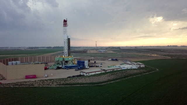 Fracking Drilling Rig in Front of a Dramatic Sky at Dusk