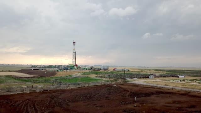 stockvideo's en b-roll-footage met fracking drilling rig in de voorkant van een dramatische hemel in de schemering - schalie