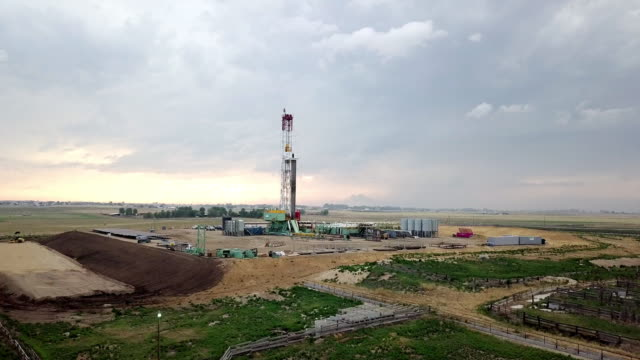 fracking drilling rig in front of a dramatic sky at dusk - fracking stock videos and b-roll footage