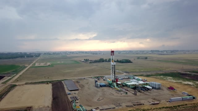 fracking drilling rig in front of a dramatic sky at dusk - drill stock videos & royalty-free footage