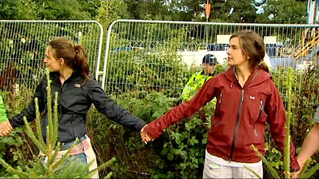 Fracking protests continue in Sussex ENGLAND Sussex Balcombe EXT Protesters along /police officers / Protesters along making human chain / Police...