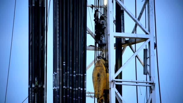 stockvideo's en b-roll-footage met fracking rig climbing worker - schalie