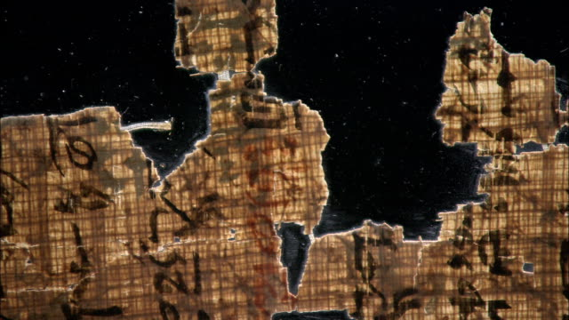 stockvideo's en b-roll-footage met fragments of papyrus occupy a black surface. - egyptische cultuur