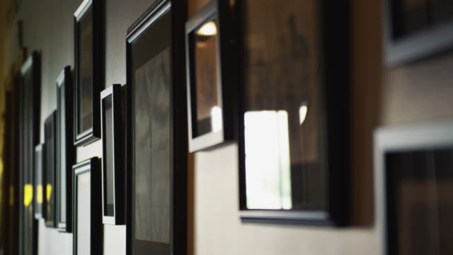 Framed art and illustrations hang beautifully in the hallway of an urban condo.