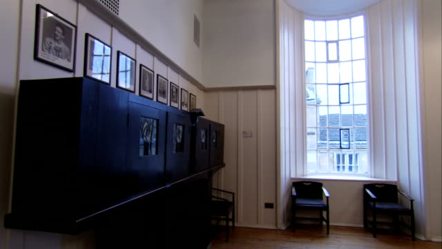 framed pictures hang above ornate shelves in a room in the glasgow school of art. available in hd. - erkerfenster stock-videos und b-roll-filmmaterial