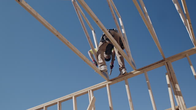 a framer standing on the skelton framed walls of a new home construction guiding the crane operator to set another truss - only mature men stock videos & royalty-free footage