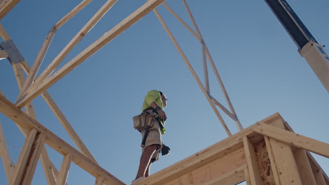 a framer standing on the skelton framed walls of a new home construction guiding the crane operator to set another truss - lowering stock videos & royalty-free footage