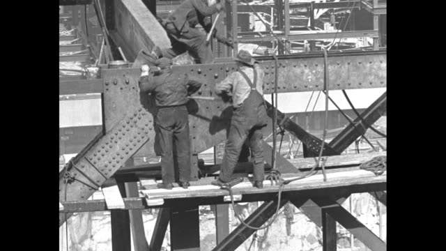 framework of building at rockefeller center with workers screwing bolts into place and construction cranes lifting steel girders into position / note... - rockefeller center stock videos & royalty-free footage