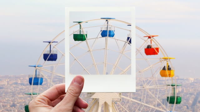 framing colorful ferris wheel in barcelona with instant print picture from personal perspective. - big wheel stock-videos und b-roll-filmmaterial