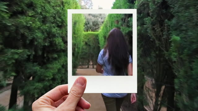 framing happy woman walking in a maze with instant print picture from personal perspective. - subjektive kamera blickwinkel aufnahme stock-videos und b-roll-filmmaterial
