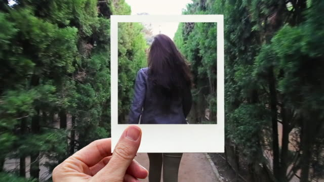 framing happy woman walking in a maze with instant print picture from personal perspective. - berühren stock-videos und b-roll-filmmaterial